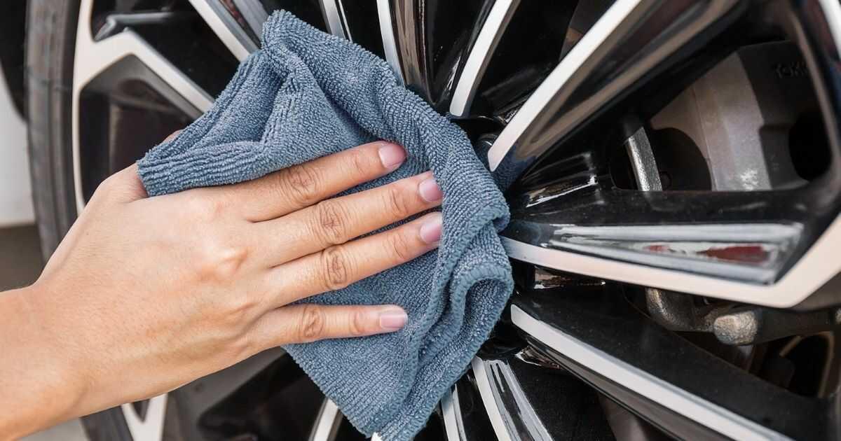 man washing car wheel
